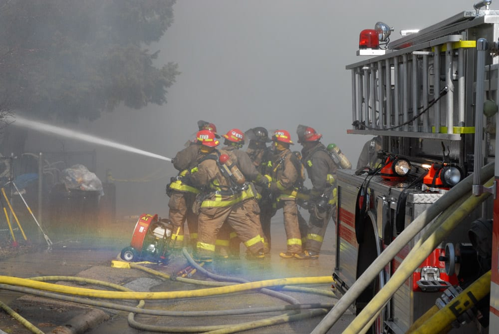 Firefighters putting water on fire